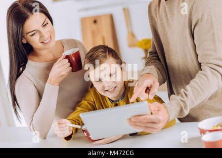 Pleasant parents showing video to son while he eating - Stock Photo