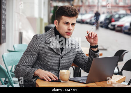 Photo of elegant businessman with brooding look sitting in cafe outside smoking cigarette and drinking cappuccino