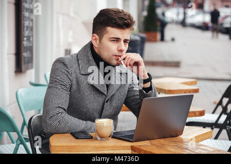 Good-looking caucasian guy with brooding look sitting in cafe outside smoking cigarette and drinking cappuccino