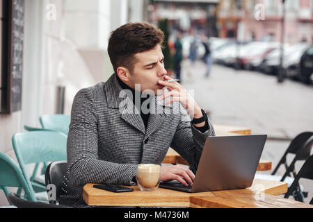 Photo of handsome man in gray coat smoking cigarette and drinking cappuccino while resting in cafe outdoors