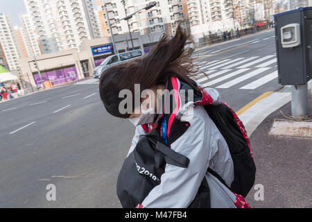 Gangneung, South Korea. 14th Feb, 2018. A volunteer fighting against the strong wind in Gangneung, South Korea, - Stock Photo