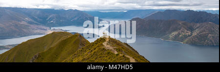 Sheep standing on mountain top in front of lake - Stock Photo