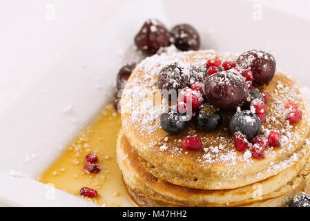 Breakfast pancakes topped with blueberries, pomegranate seeds, cherries and icing sugar (powdered sugar) and maple - Stock Photo