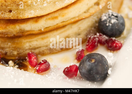 Breakfast pancakes with blueberries, pomegranate seeds and maple syrup isolated on a white background with very - Stock Photo