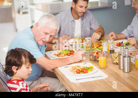 Grandfather assisting grandson while having breakfast - Stock Photo
