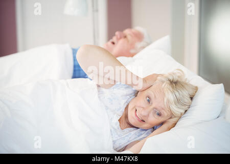 Senior woman blocking ears while man snoring on bed - Stock Photo