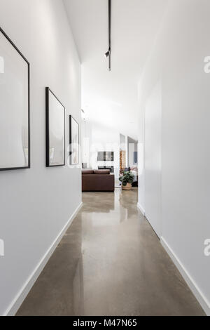 Bright white contemporary new home entrance hall to living room - Stock Photo