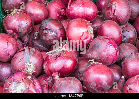 Background of red spanish onions seen at a market - Stock Photo