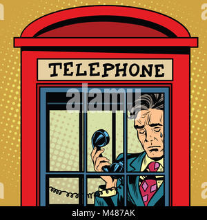 Retro man crying in a phone booth - Stock Photo