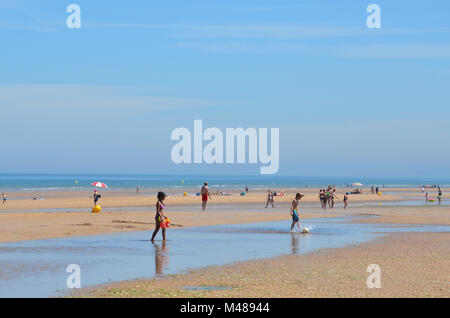 Children enjoy a sunny summer day playing soccer on beach, while tourist walk along the shore -  Arromaches-les - Stock Photo