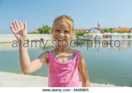Little girl walks near Lower bridge, Nin, Croatia - Stock Photo