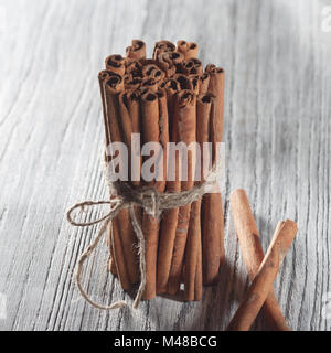 Cinnamon sticks isolated on white wooden table - Stock Photo