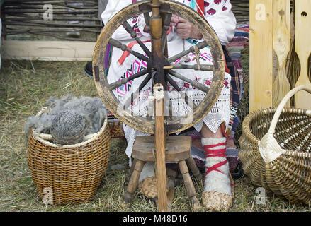An elderly woman spinning thread on a spinning wheel. - Stock Photo