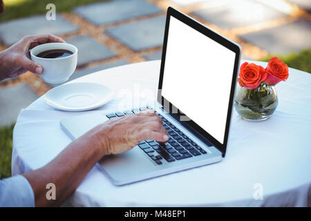 Close up of masculine hands using laptop and having coffee - Stock Photo