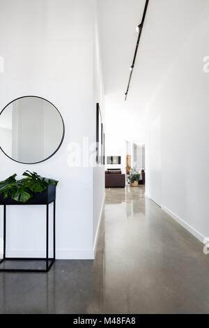 Contemporary new home entry and hallway with polished concrete floors - Stock Photo
