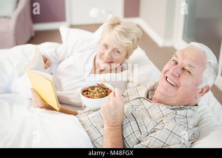 Portrait of couple reading book while having breakfast on bed - Stock Photo