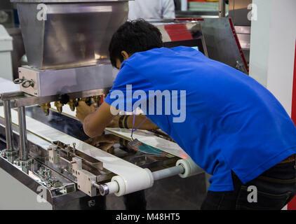 Food worker operate bakery making machine - Stock Photo