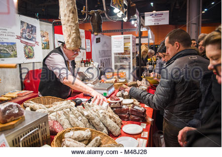 People buying meat from butcher at covered market - Stock Photo