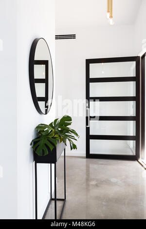 Glass entry door to foyer with planter and round mirror - Stock Photo