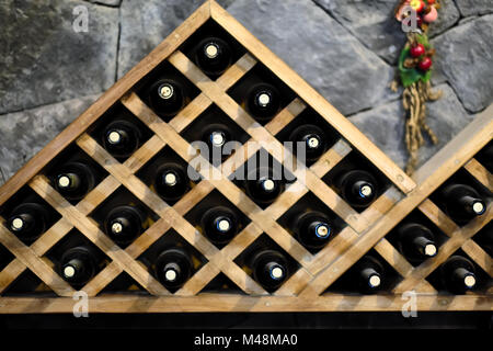 Wine bottles stacked on wooden racks - Stock Photo