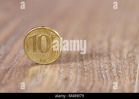 Gold coin ten robles worth on the wooden floor - Stock Photo