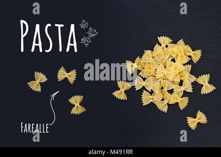 Uncooked Italian pasta Farfalle on black slate stone background - Stock Photo