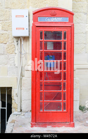 Red telephone cabin in the medieval old town of Victoria in Gozo island, Malta - Stock Photo