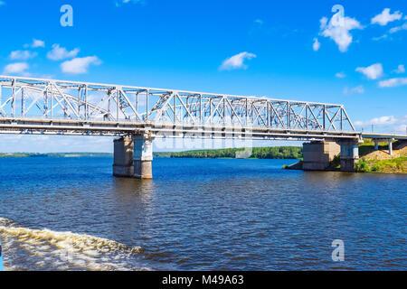 Railway bridge over the river on a concrete base - Stock Photo