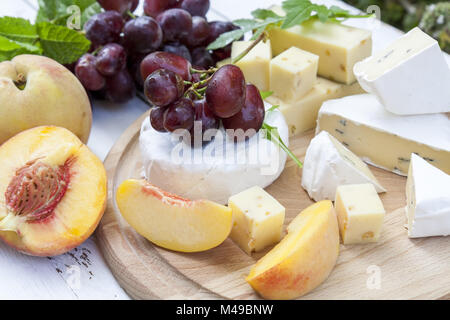 Different delicious cheeses and fruits on wooden round board - Stock Photo
