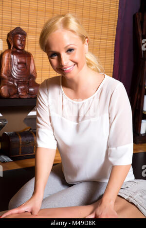 A young beautiful masseuse applying a massage - Stock Photo