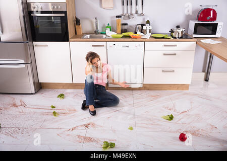 Unhappy Young Woman Sitting On Dirty Kitchen Floor At Home - Stock Photo