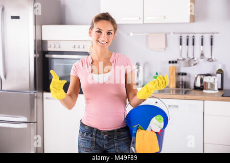 Portrait Of A Happy Woman Wearing Gloves Carrying Cleaning Equipments In Bucket Standing In Kitchen - Stock Photo
