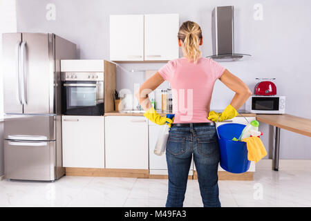 Woman Wearing Gloves Carrying Cleaning Equipments In Bucket Standing In Kitchen - Stock Photo