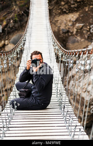 Photographer on footbridge, W Trek. Torres del Paine National Park, Patagonia, Chile. January 2014. Model released. - Stock Photo