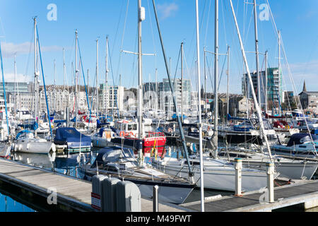 Sutton Harbour Plymouth on a sunny day in February with yachts moored on the pontoons - Stock Photo