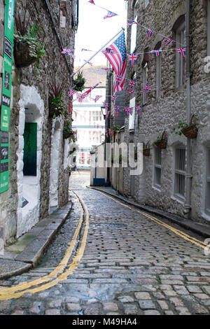 Cobbled street in the Barbican area of Plymouth with British and American flags flying, leading down to the marina, - Stock Photo