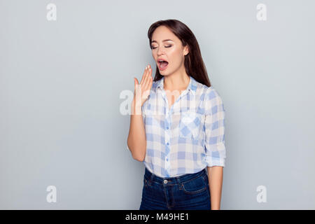 Portrait of tired, bored, nice, attractive woman in checkered shirt, closing her open mouth, she wants to sleep, - Stock Photo