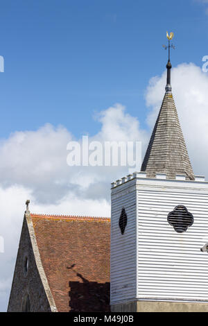 Roof and tower of English country church set against white clouds and blue sky - Stock Photo