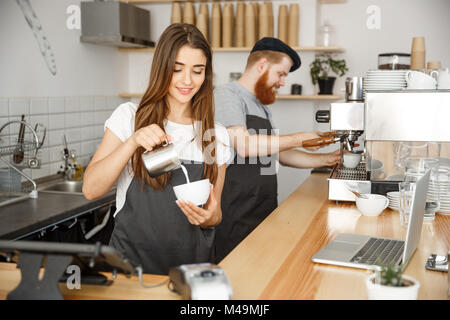 Coffee Business Concept - close-up lady barista in apron preparing and pouring milk into hot cup while standing - Stock Photo