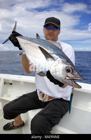 Happy  fisherman holding a tuna fish. Deep sea fishing, big game fishing, catch of fish. - Stock Photo