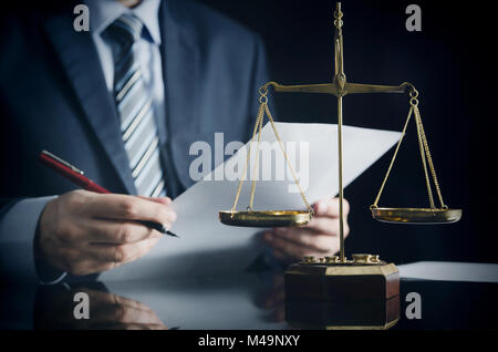 Lawyer or attorney works in his office. Scales on the desk - Stock Photo