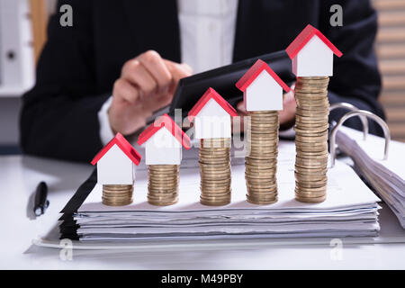 Midsection Of Businesswoman Calculating Invoice With House Models Arranged On Stacked Coins - Stock Photo