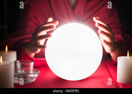 Beautiful Young Fortuneteller Holding Hands Around A Glowing Ball - Stock Photo