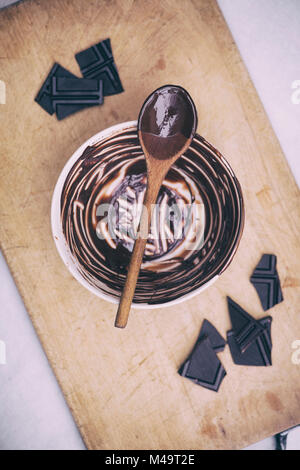 Melted dark chocolate and wooden spoon on a ceramic mixing bowl. Vintage filter applied - Stock Photo