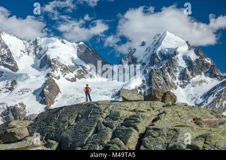 Hiker beneath Piz Bernina and Piz Rosbeg, Fuorcla Surlej, Berniner Alps, Graubunden, Switzerland. - Stock Photo