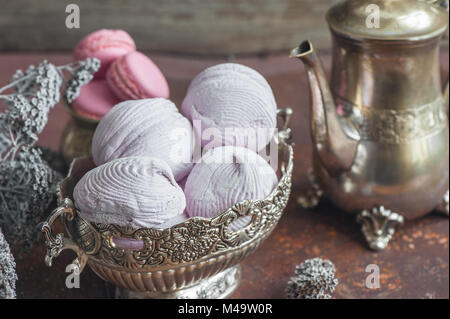 Freshly baked marshmallows and macaroons on metal plate with small white flowers and tea appliances composition - Stock Photo