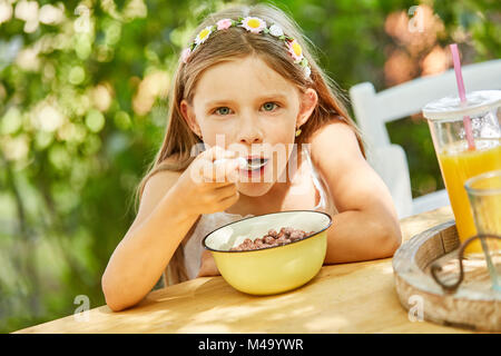 Hungry girl is eating healthy cereal for breakfast in kindergarten - Stock Photo