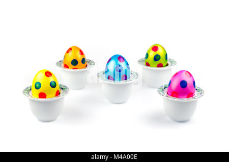 Painted easter eggs standing in porcelain egg cups on white - Stock Photo