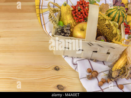 Autumn arrangement in a basket on wooden table - Stock Photo