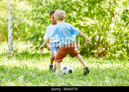Two boys in duel while playing football in the sport club in the park - Stock Photo